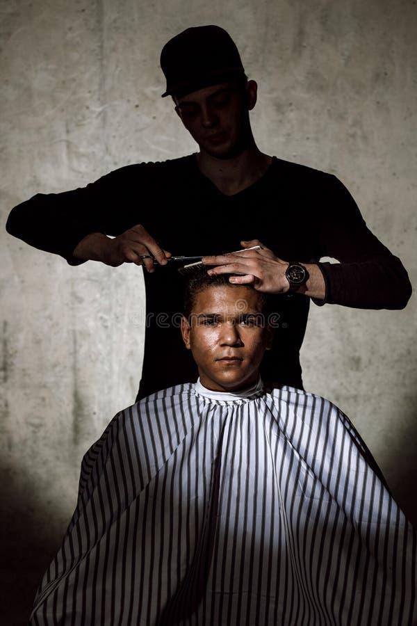 El peluquero elegante vestido en negro tijeras de la ropa el pelo del hombre en una barbería contra un muro de cemento fotografía de archivo libre de regalías