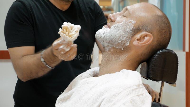 El peluquero está afeitando a su cliente de la vieja manera de la moda fotografía de archivo