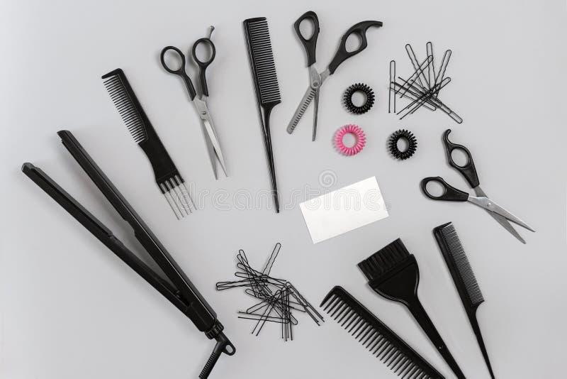 El peluquero fijó con los diversos accesorios en fondo gris fotografía de archivo libre de regalías