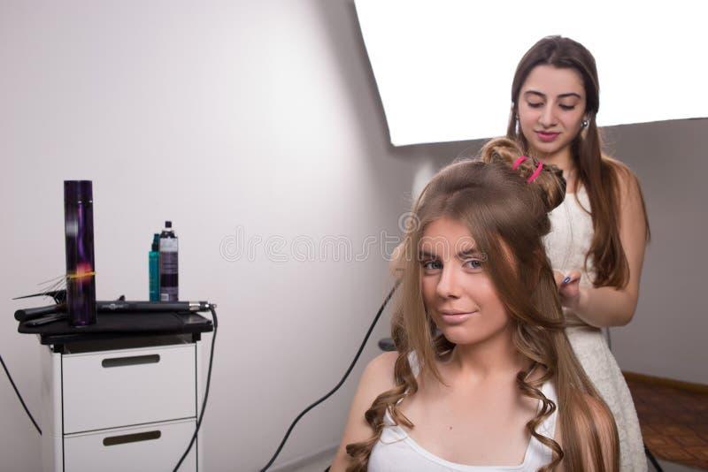 El peluquero hace el estilo de pelo de la mujer adentro fotos de archivo