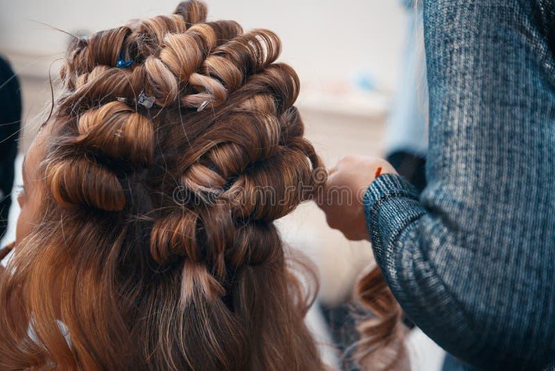 El peluquero hace extensiones del pelo a una chica joven imágenes de archivo libres de regalías