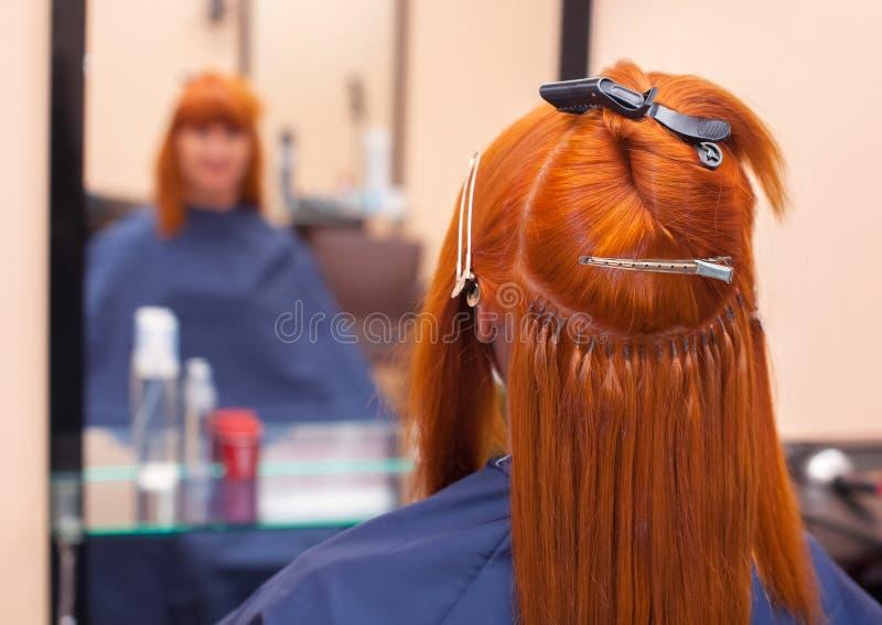 El peluquero hace extensiones del pelo a una muchacha joven, pelirroja, en un salón de belleza fotos de archivo