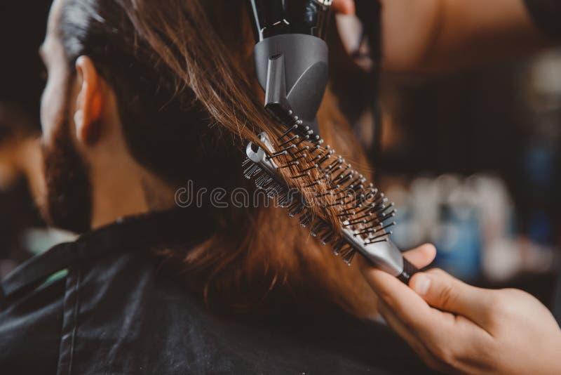 El peluquero hace el pelo que dise?a para servir con el hairdryer y el peine imagenes de archivo