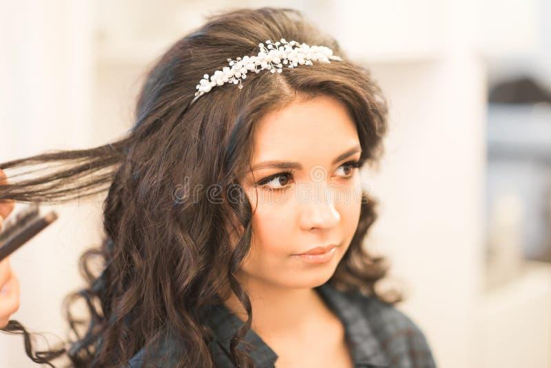 El peluquero hace un peinado a la novia imagen de archivo