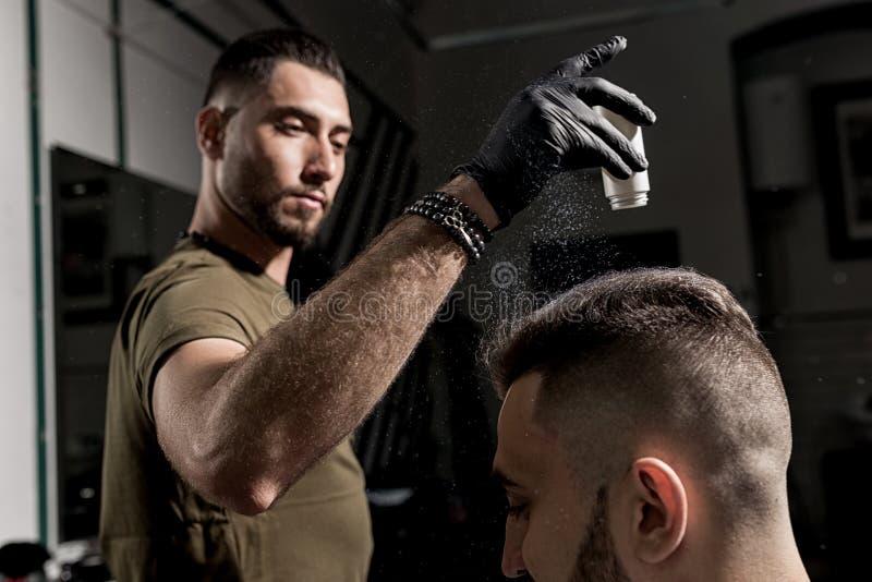 El peluquero hermoso está fijando diseñar del hombre barbudo joven brutal con un styler seco en una barbería foto de archivo