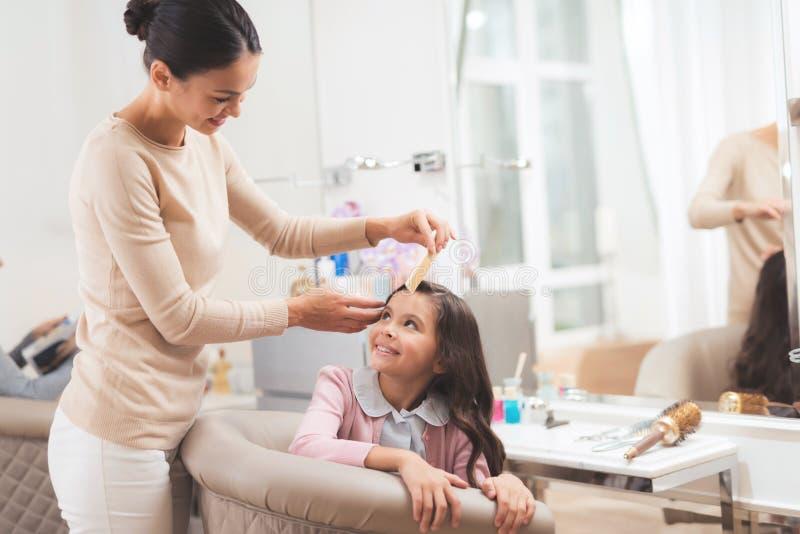 El peluquero que hace el pelo que diseña a una pequeña muchacha oscuro-cabelluda La muchacha se está sentando en la silla del sal fotografía de archivo libre de regalías