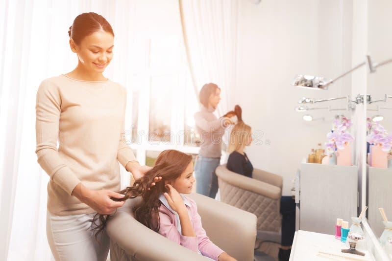 El peluquero que hace el pelo que diseña a una pequeña muchacha oscuro-cabelluda La muchacha se está sentando en la silla del sal foto de archivo