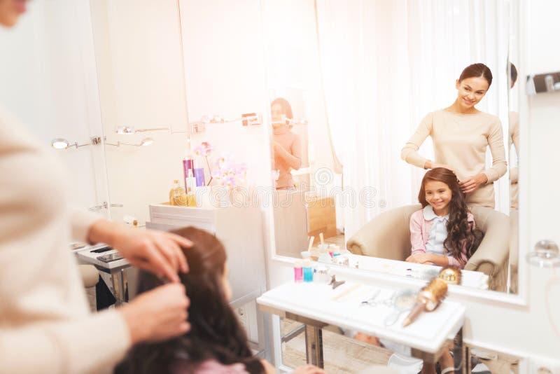 El peluquero que hace el pelo que diseña a una pequeña muchacha oscuro-cabelluda La muchacha se está sentando en la silla del sal fotos de archivo libres de regalías