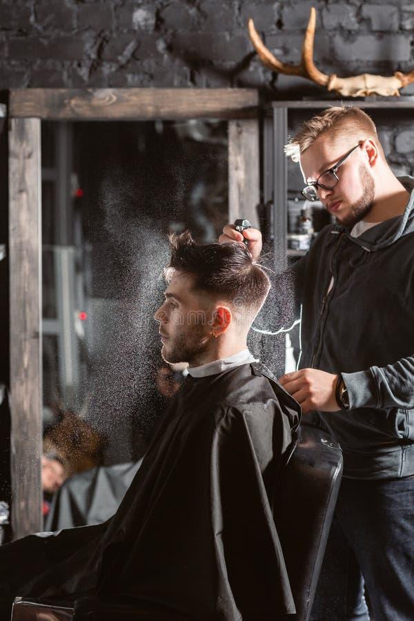 El peluquero roc?a el agua potable en la cabeza en barber?a La herramienta profesional del condensador de ajuste corta la barba y imágenes de archivo libres de regalías