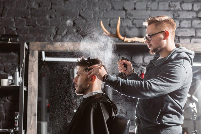 El peluquero roc?a el agua potable en la cabeza en barber?a La herramienta profesional del condensador de ajuste corta la barba y imagen de archivo