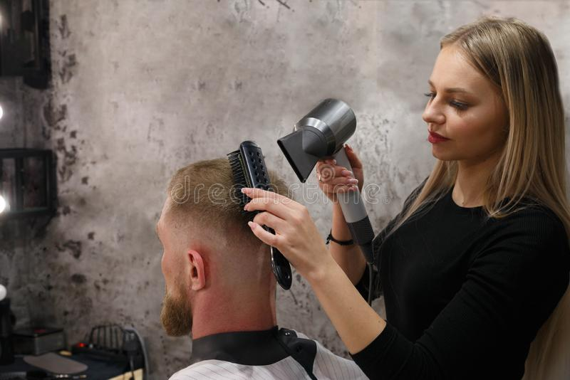 El peluquero seca el pelo del cliente con un secador de pelo y un cepillo para el pelo en la peluquería fotos de archivo