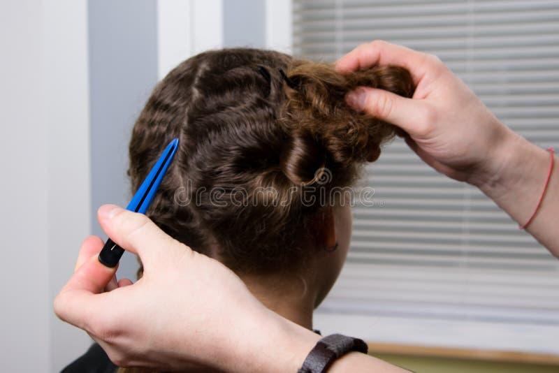 El peluquero sostiene una pinza de pelo en su mano y hace un peinado para el niño fotos de archivo