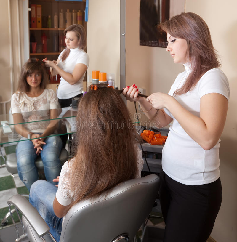El peluquero trabaja en el pelo de la mujer foto de archivo