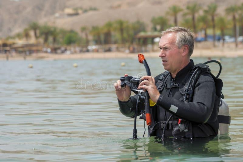 El pensionista es buceador subacuático con el aparato respiratorio en el mar Buceador recreativo del respiración-control en el eq foto de archivo