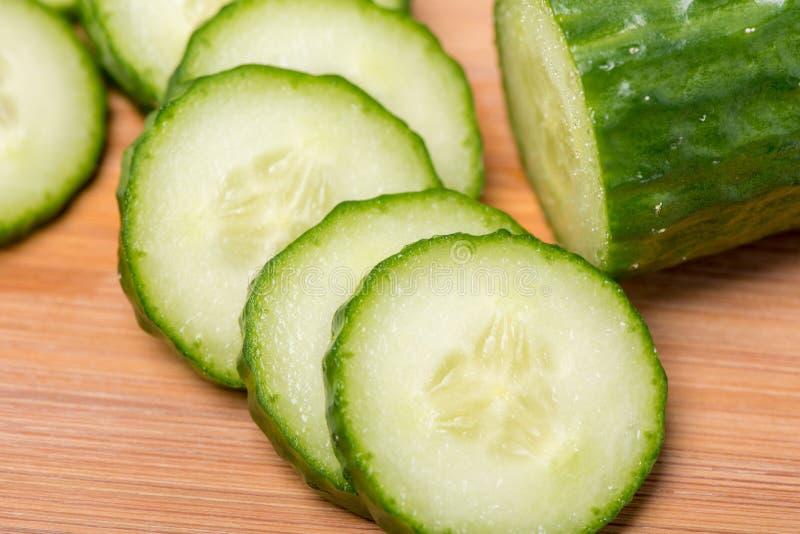 El pepino verde maduro cortó en círculos en un tablero de madera en un blanco fotos de archivo