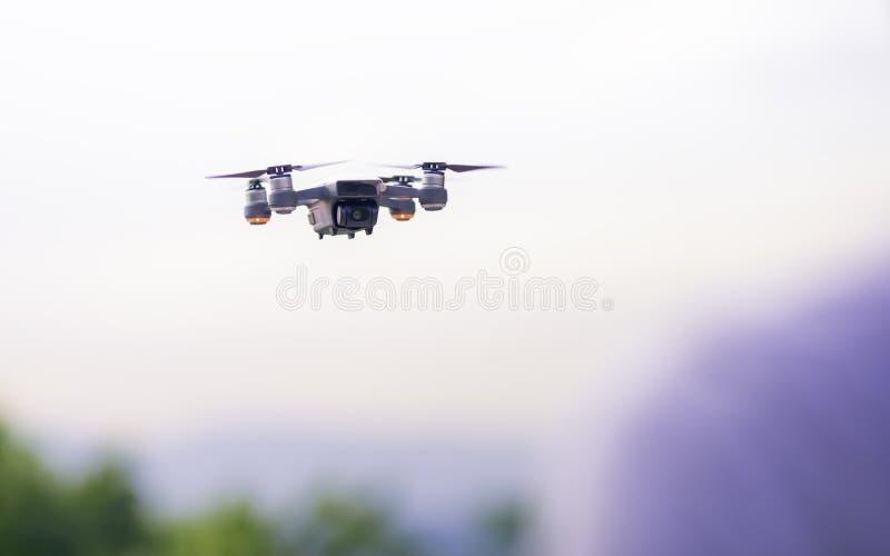 El pequeño abejón elegante Quadrocopter está volando en el aire, fondo blanco del cielo foto de archivo