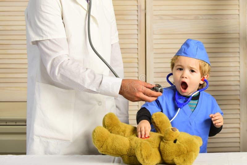 El pequeño ayudante examina el oso de peluche Concepto de la salud y de la niñez foto de archivo
