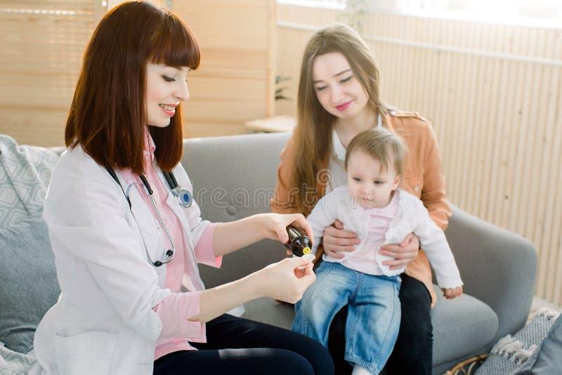 El pequeño bebé acepta para beber el jarabe de la medicina con la cuchara del médico de cabecera en casa imagen de archivo