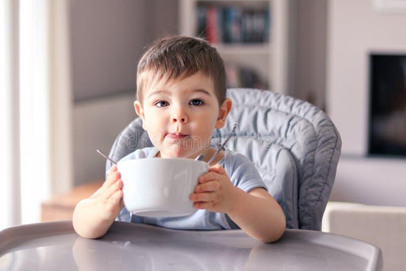 El pequeño bebé agradecido adorable con la cara manchada apenas acabó su comida sabrosa y sostiene el cuenco blanco imagen de archivo