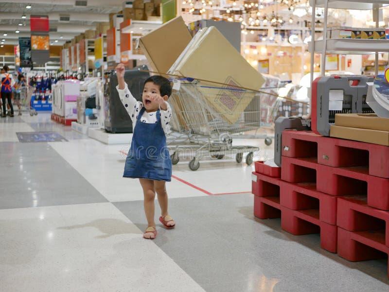 El pequeño bebé asiático está en un buen humor y goza el caminar en una alameda de compras fotos de archivo