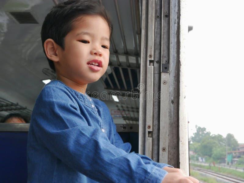 El pequeño bebé asiático goza el colocarse derecho por una ventana del tren y el tener de los azotes del viento contra su cara imagenes de archivo