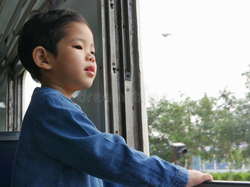 El pequeño bebé asiático goza el colocarse derecho por una ventana del tren y el tener de los azotes del viento contra su cara imágenes de archivo libres de regalías