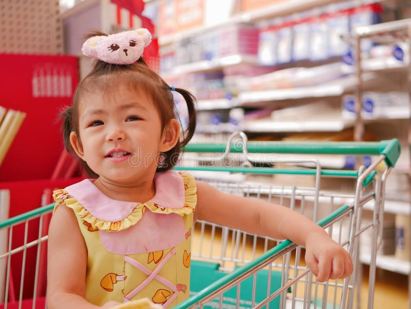 El pequeño bebé asiático goza el estar en un carro de la compra que espera a su madre para hacer compras foto de archivo libre de regalías