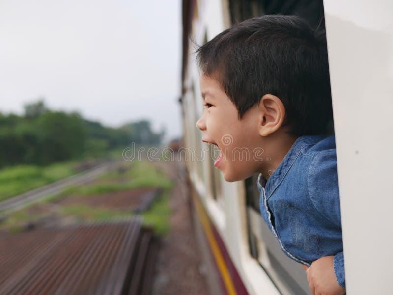 El pequeño bebé asiático goza el gritar de una ventana del tren y el tener de los azotes del viento contra su cara foto de archivo libre de regalías