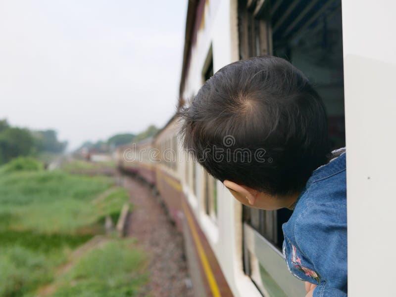El pequeño bebé asiático goza el pegar de su cabeza fuera de una ventana del tren y el tener de los azotes del viento contra su c imagen de archivo