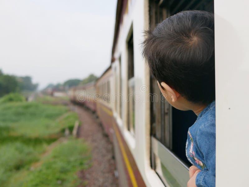 El pequeño bebé asiático goza el pegar de su cabeza fuera de una ventana del tren y el tener de los azotes del viento contra su c imagen de archivo libre de regalías