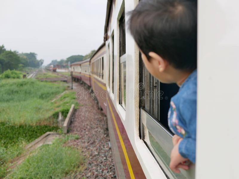 El pequeño bebé asiático goza el pegar de su cabeza fuera de una ventana del tren y el tener de los azotes del viento contra su c fotografía de archivo