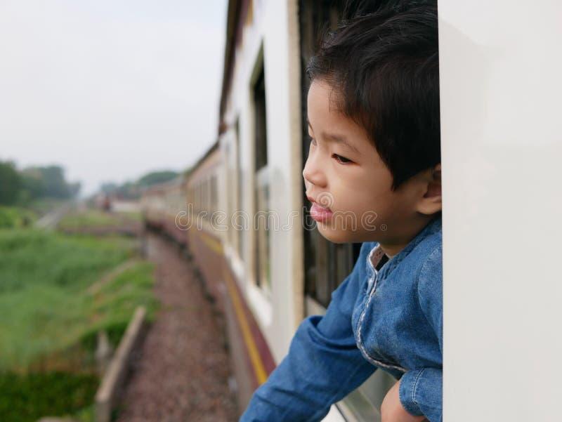 El pequeño bebé asiático goza el pegar de su cabeza fuera de una ventana del tren y el tener de los azotes del viento contra su c foto de archivo libre de regalías