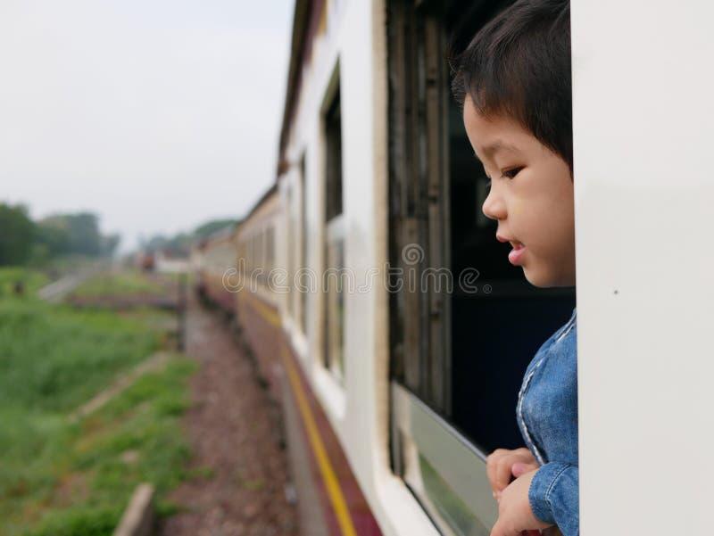El pequeño bebé asiático goza el pegar de su cabeza fuera de una ventana del tren y el tener de los azotes del viento contra su c imagenes de archivo