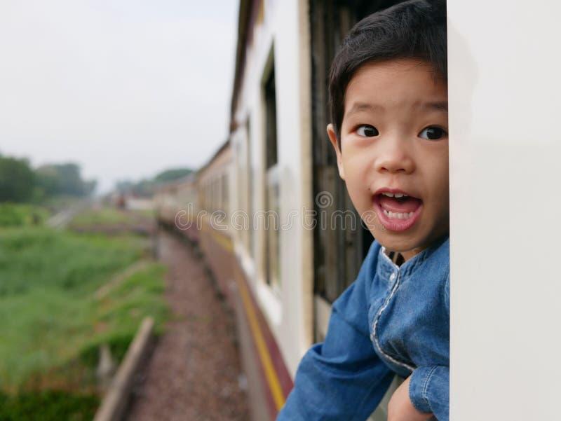 El pequeño bebé asiático goza el pegar de su cabeza fuera de una ventana del tren y el tener de los azotes del viento contra su c fotografía de archivo libre de regalías