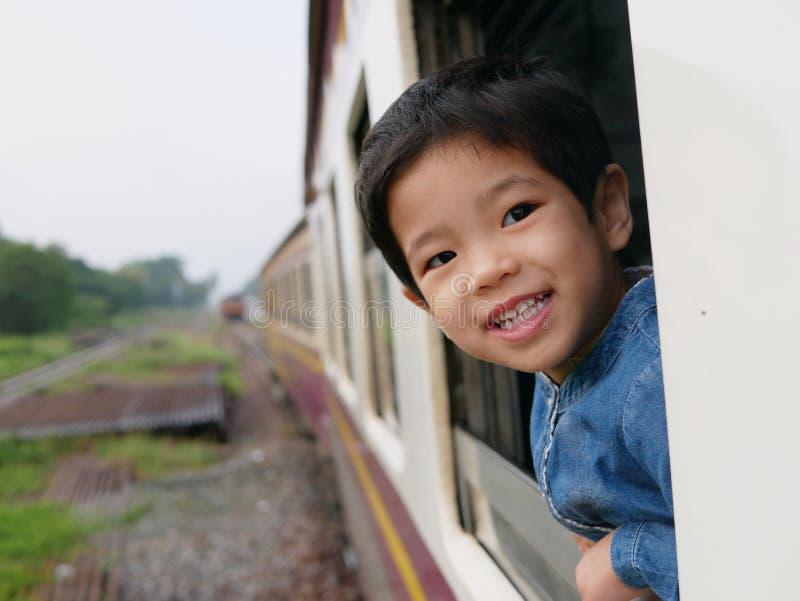 El pequeño bebé asiático goza el pegar de su cabeza fuera de una ventana del tren y el tener de los azotes del viento contra su c foto de archivo