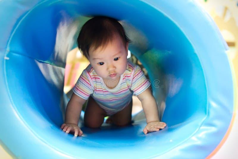 El pequeño bebé asiático sonriente joven goza el jugar y el arrastrarse en tubo azul en el patio del niño imagenes de archivo