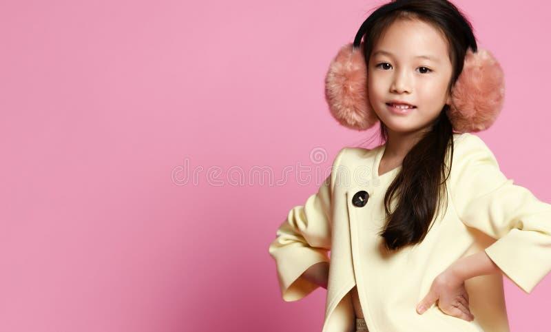 El pequeño bebé coreano en chaqueta amarilla de la moda y vestido púrpura en oído caliente suave desperdicia los auriculares imágenes de archivo libres de regalías
