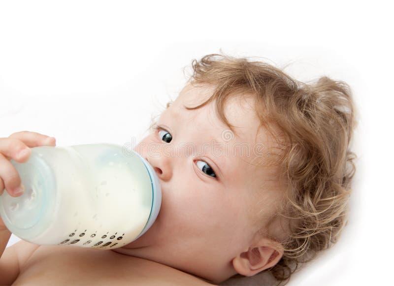 El pequeño bebé de pelo rizado chupa una botella fotografía de archivo