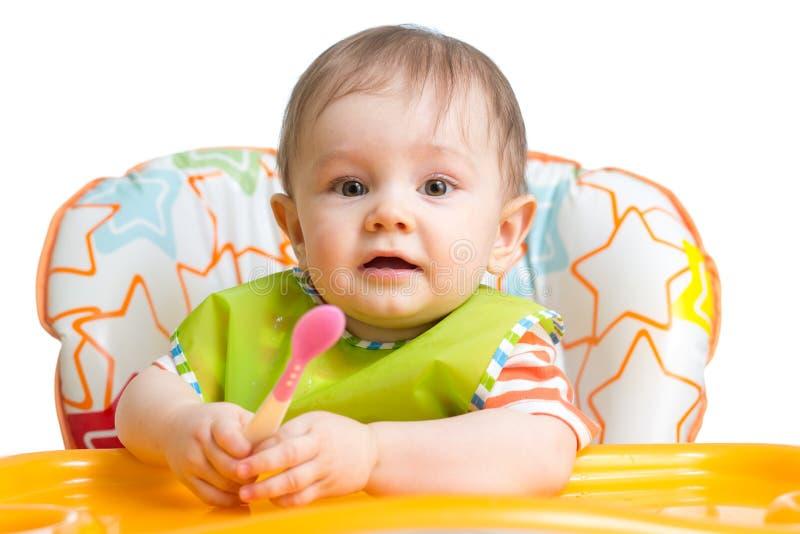 El pequeño bebé está comiendo Muchacho del niño que se sienta con la cuchara en la tabla foto de archivo libre de regalías