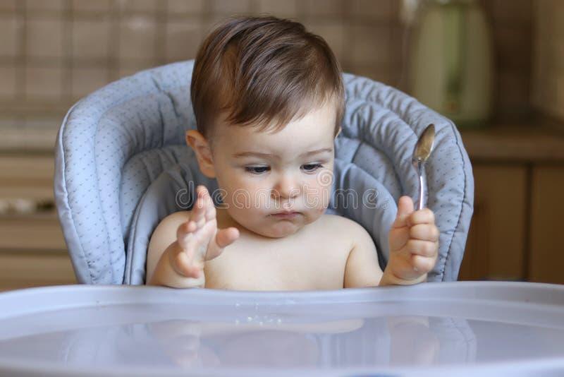 El pequeño bebé hambriento lindo sostiene la cuchara en su mano y mira la comida que espera de la tabla vacía para fotos de archivo libres de regalías