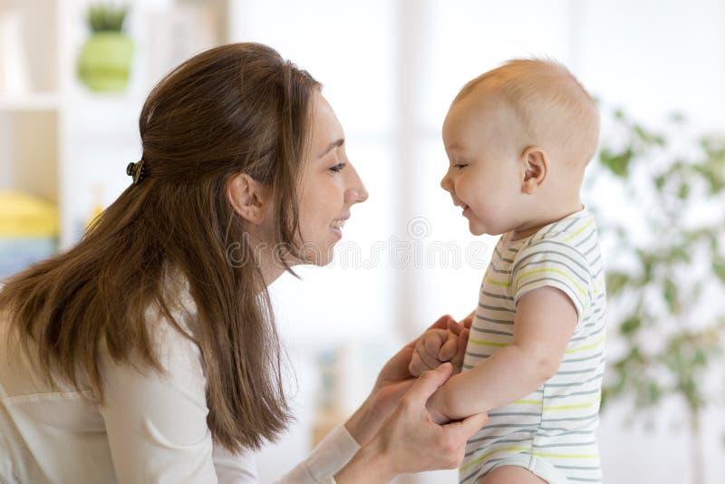 El pequeño bebé lindo juega con su mamá joven imagen de archivo