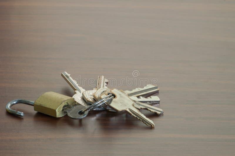 El pequeño bloqueo de teclas en la tabla de madera, llavero en el CCB de la tabla imagen de archivo libre de regalías