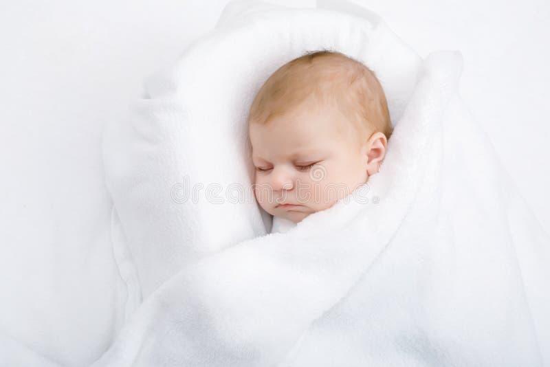 El pequeño dormir recién nacido lindo del bebé envuelto en manta imágenes de archivo libres de regalías