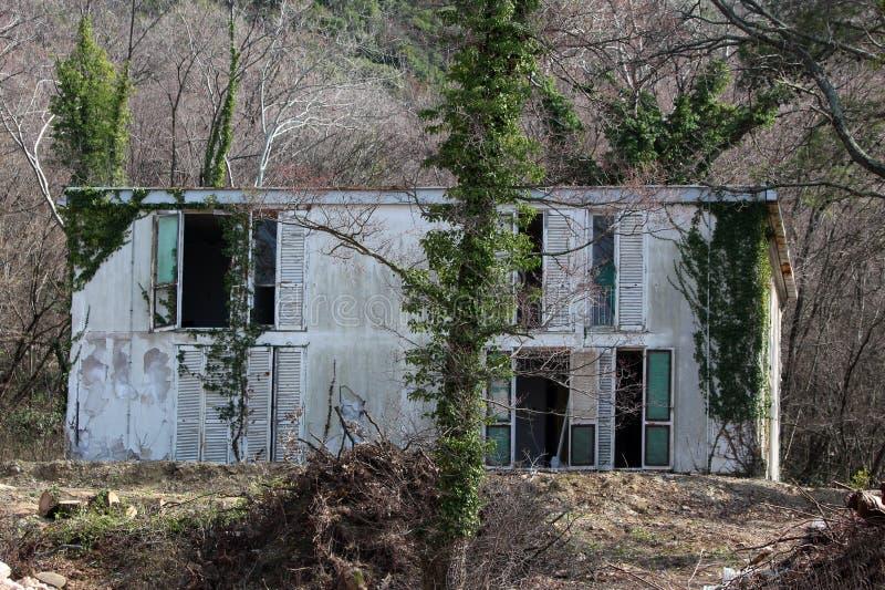 El pequeño edificio viejo abandonado del hotel con la fachada agrietada y las ventanas quebradas rodeadas con los árboles altos y fotografía de archivo