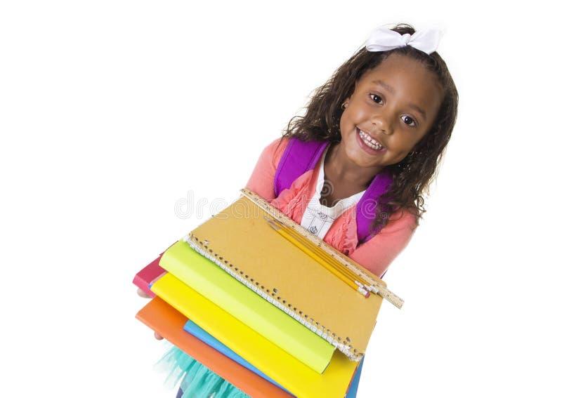 El pequeño estudiante diverso lindo lleva los libros de escuela imagen de archivo