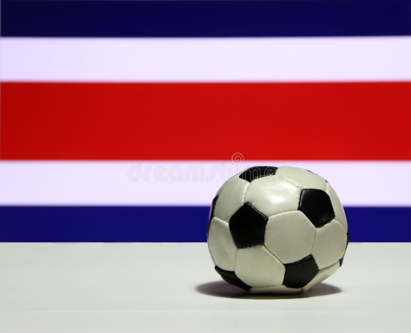 El pequeño fútbol en el piso blanco con hacia fuera enfoca el color rojo y azul blanco del fondo de la bandera de la nación de Co imagenes de archivo