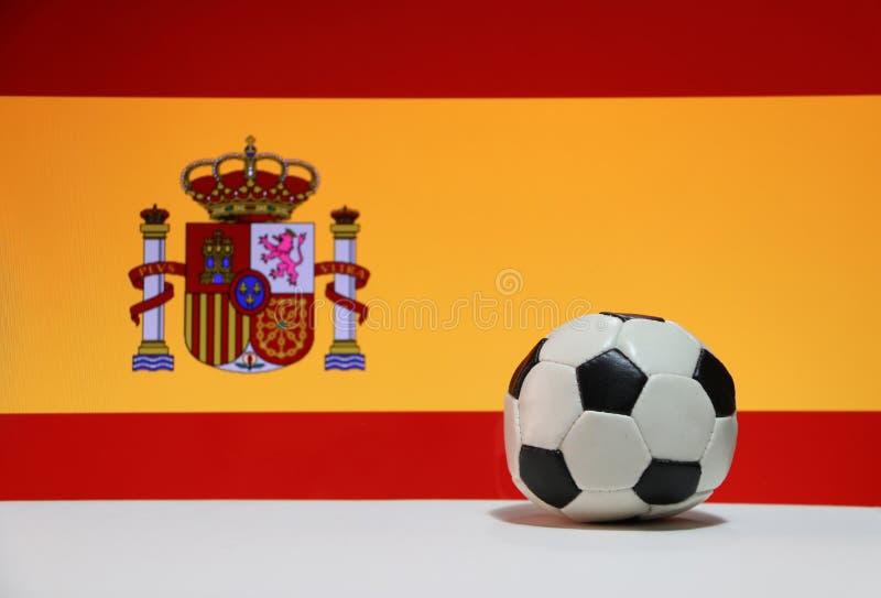 El pequeño fútbol en el piso blanco y la nación española señalan el fondo por medio de una bandera fotografía de archivo