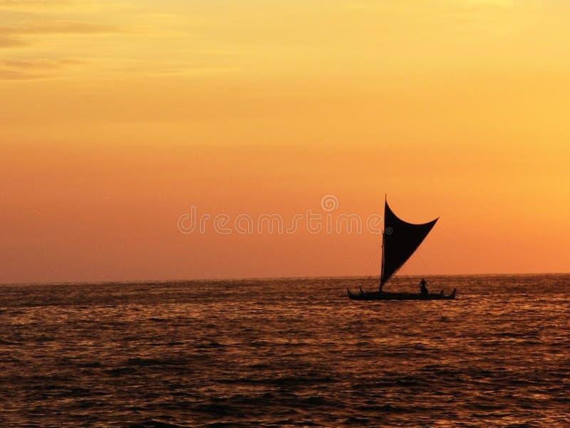 El pequeño fondo de la navegación de la silueta del barco de vela quemó puesta del sol anaranjada imagen de archivo libre de regalías