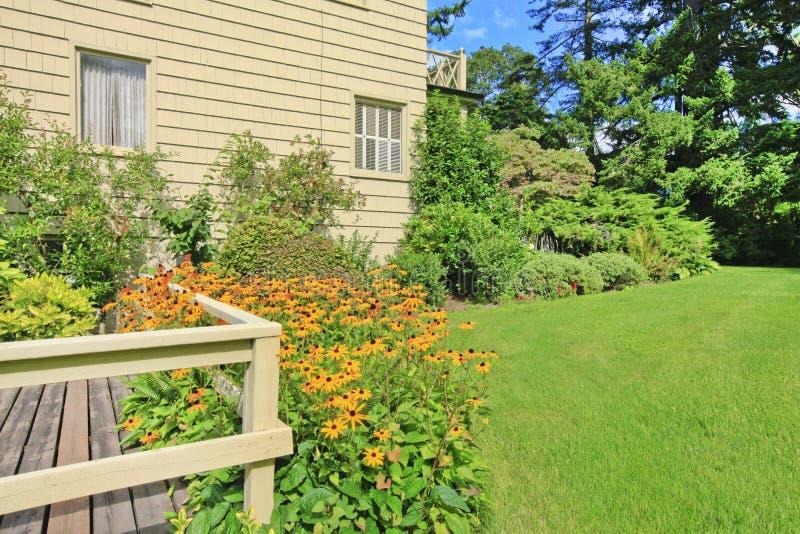 El pequeño hogar americano con la luz exterior y una hierba grande llenó el césped imagenes de archivo