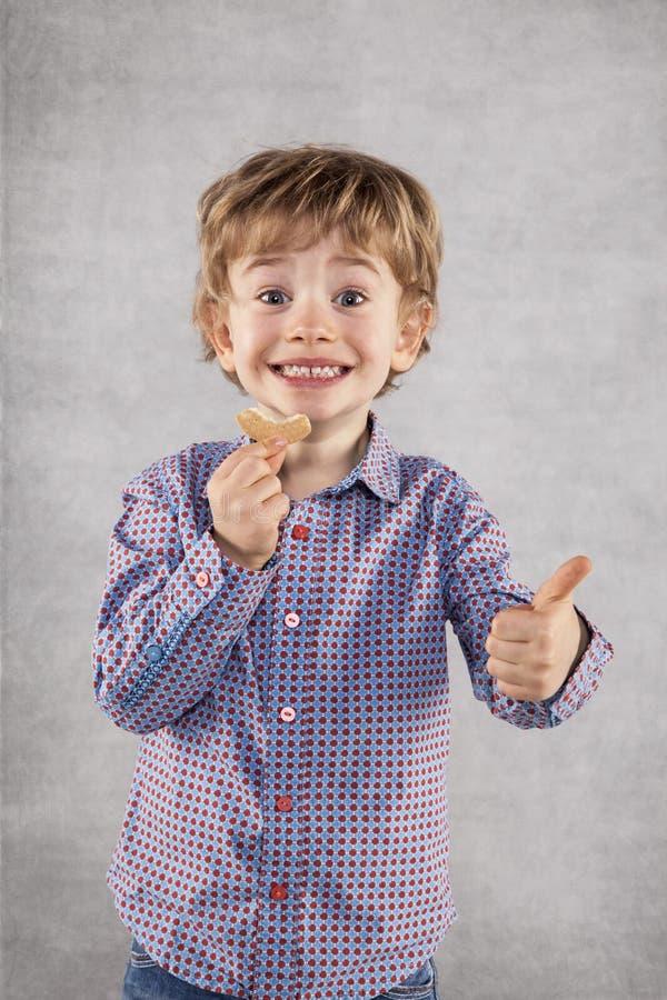 El pequeño hombre de negocios recomienda las tortas sabrosas para el almuerzo, pulgares para arriba imagen de archivo